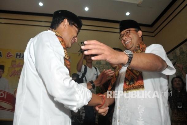 Gubernur dan Wakil Gubernur DKI Jakarta Terpilih Anies Baswedan (kanan) dan Sandiaga Uno (kiri) menghadiri acara selamatan dan doa bersama yang digelar Partai Keadilan Sejahtera (PKS) di Hotel Grand Cempaka, Jakarta, Ahad (15/10).
