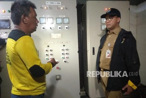 Gubernur DKI Jakarta Anies Baswedan saat meninjau panel listrik mesin pompa yang rusak ditemani Operator Pompa Mulyadi.