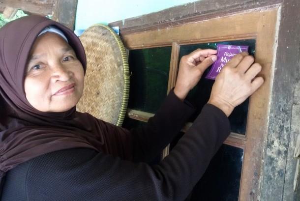 Ibu Keni sedang menempelkan stiker Amartha di warung nasi uduk miliknya