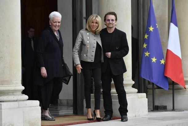 Ibu Negara Prancis Brigitte Macron (tengah) berpose dengan penyanyi rock Bono, (24/7). Bono berada di Istana Elysee Paris untuk bertemu dengan Presiden Prancis Emmanuel Macron.
