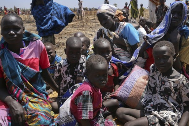 In this photo taken Saturday, Feb. 25, 2017 and released by the World Food Programme (WFP), a family waits for food assistance to be distributed in Thonyor, Leer County, one of the areas in which famine has been declared, in South Sudan.