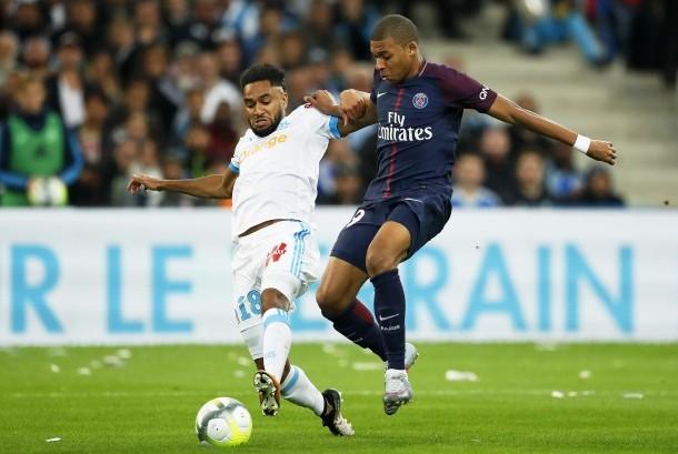 Jordan Amavi (kiri) dari Olympique Marseille mencoba menghalangi pemain Paris Saint-Germain Kylian Mbappe (kanan) pada pertandingan Ligue 1 antara kedua tim di Stadion Velodrome, Marseille, Prancis, Ahad (22/10).