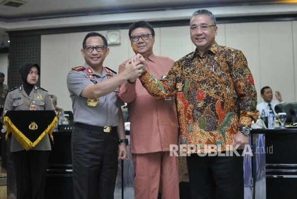Kapolri Jenderal Pol Tito Karnavian (kiri) bersama Menteri Dalam Negeri Tjahjo Kumolo (tengah) dan Menteri Desa, Pembangunan Daerah Tertinggal dan Transmigrasi Eko Putro Sandjojo (kanan) berjabat tangan seusai penandatangani nota kesepahaman mengenai dana desa di Mabes Polri, Jakarta, Jumat (20/10).
