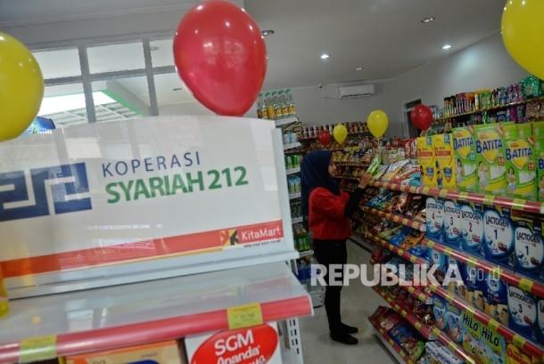 Karyawan menata produk di Mini Market KitaMart di Jatiasih, Bekasi, Jawa Barat, Rabu (29/3).