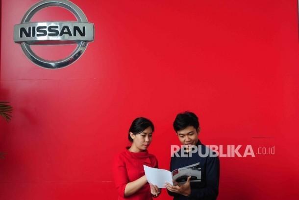 Karyawati melayani calon pembeli di diler PT Mitra Pinasthika Mustika Auto (MPM Auto) Nissan-Datsun di Alam Sutra, Tanggerang, Banten, Senin (28/3).