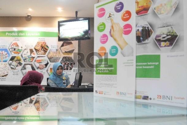 Karyawati melayani nasabah di Banking Hall BNI syariah, Jakarta, Selasa (5/1).