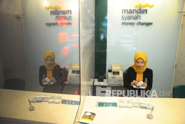 Karyawati menghitung dolar AS di Banking Hall Bank Syariah Mandiri, Jakarta, Selasa (18/4).