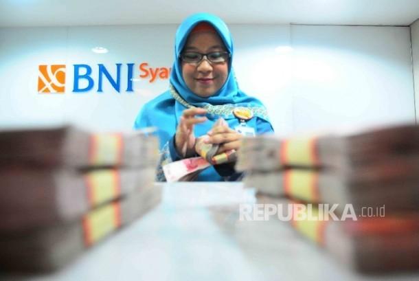 Karyawati menghitung uang di banking Hall bank BNI Syariah, Jakarta. ilustrasi