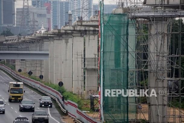 Kendaraan melintas di samping proyek infrastruktur transportasi massal kereta ringan atau Light Rail Transit (LRT) di kawasan Halim, Jakarta. (ilustrasi).