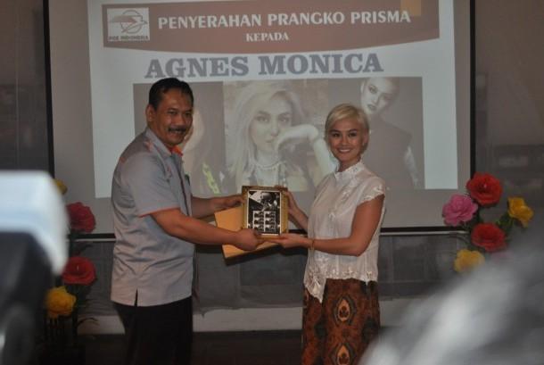 Kepala Regional 4 Jakarta Pos Indonesia Pupung Purnama (kiri) menyerahkan prangko prisma kepada penyanyi Agnez Mo (kanan) sebagai brand ambassador Pos Indonesia di Kantor Pos Fatahilah Kota Tua Jakarta Barat, Senin (25/9).