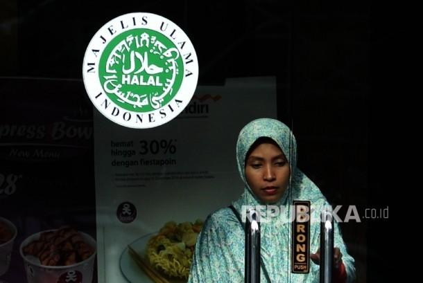 Logo halal Majelis Ulama Indonesia (MUI) terpampang dipintu masuk salah satu restoran cepat saji di Jakarta, Ahad (16/10).