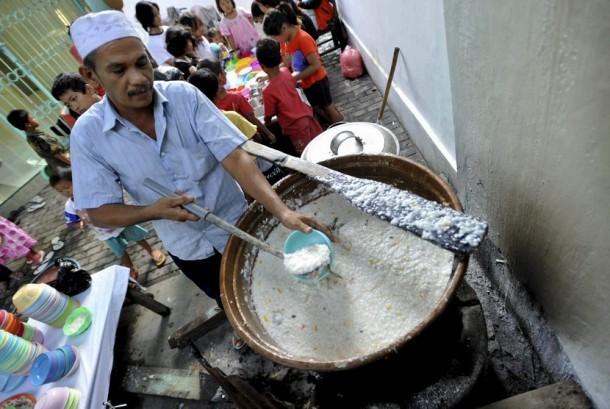Pengurus masjid menuangkan bubur India ke dalam mangkuk untuk hidangan berbuka puasa, di Masjid Jami Pekojan Semarang, Senin (30/6).   (Antara/R. Rekotomo)