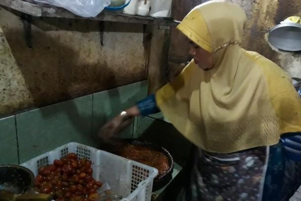 Mbok Nah sedang membuat sambal ranti untuk teman makan nasi tempong.