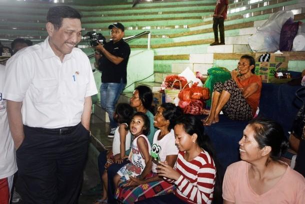 Menko Kemaritiman Luhut Binsar Panjaitan (kiri) berbincang dengan pengungsi letusan Gunung Agung di GOR Suweca, Klungkung, Bali, Minggu (24/9).