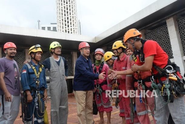 Menteri Agama Lukman Hakim Saifuddin berjabat tangan dengan para relawan saat meninjau proses membersihkan Masjid Istiqlal, Jakarta, Ahad (19/2).