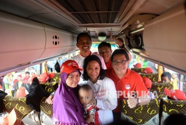 Menteri BUMN Rini Soemarno (tengah) bersama Dirut Telkom Alex Sinaga (kanan) berfoto bersama pemudik PT Telokm sebelum pelepasan Mudik Bareng Guyub Rukun BUMN di TMII,Jakarta, Senin (19/6).