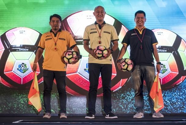 Model menunjukan kaos wasit dan bola yang akan digunakan dalam penyelenggaraan kompetisi Liga 1 di Jakarta, Senin (10/4).