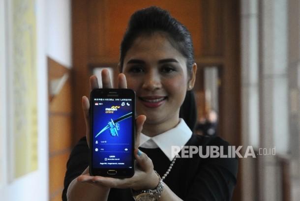 Model menunjukan layanan Mandiri Online saat peluncuran mandiri Online di Plasa Mandiri, Jakarta, Senin (21.3).