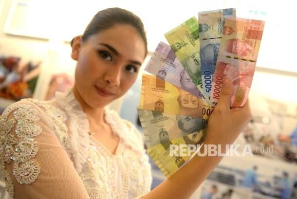 Model menunjukan uang Rupiah kertas wajah baru usai peresmian pengeluaran dan pengedaran uang Rupiah Tahu Emisi 2016 di Bank Indonesia, Jakarta, Senin (19/12).