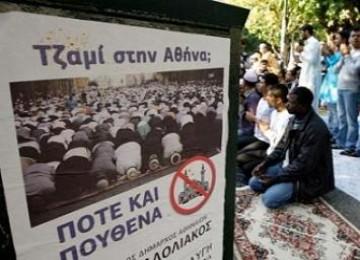 Muslim Yunani sholat di jalanan di dekat poster anti pembangunan masjid