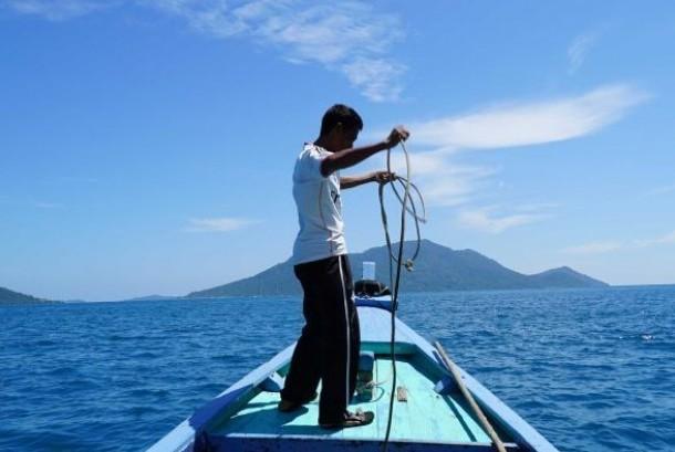 Nelayan bernama Idris (42) di atas perahunya di perairan Kepulauan Natuna.