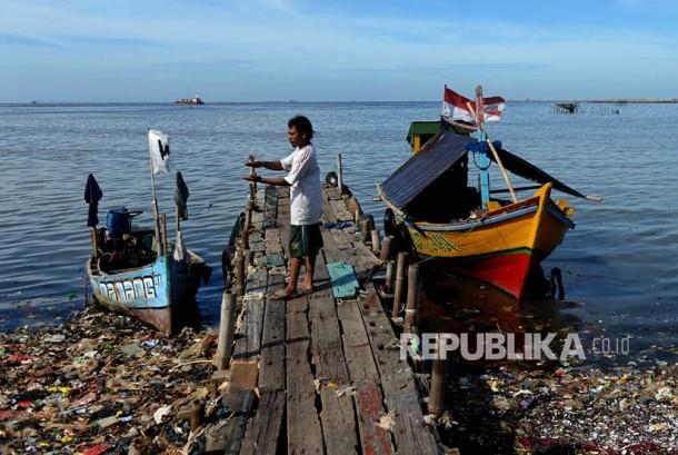 Nelayan kerang hijau Muara Angke menambatkan perahunya di dermaga. Di garis cakrawala proses reklamasi telah menggusur tempat-tempat peterenakan kerang hijau di Teluk Jakarta.