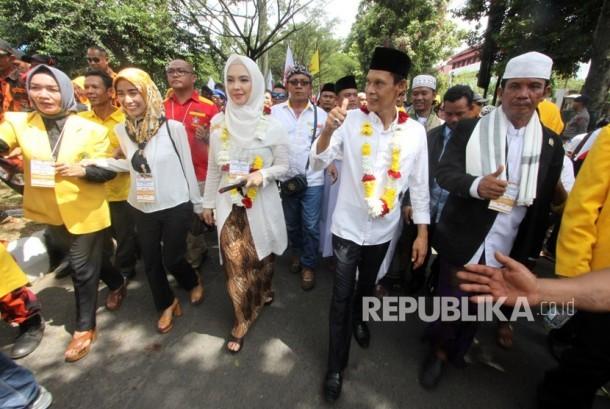 Pasangan bakal Calon Bupati Bogor Ade Ruhandi (kanan) dan Inggrid Kansil (kiri) bersama pendukungnya berjalan menuju KPUD Kabupaten Bogor, Cibinong, Bogor, Jawa Barat,Rabu (10/1).