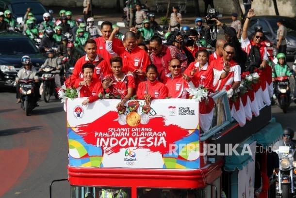 Pebulu tangkis ganda campuran peraih medali emas Olimpiade Brasil, Tontowi Ahmad dan Liliyana Natsir bersama sejumlah atlet dan offsial berada diatas bus tingkat terbuka Bandros menuju Istana Negara di Bundaran HI Jakarta, Rabu (24/8).