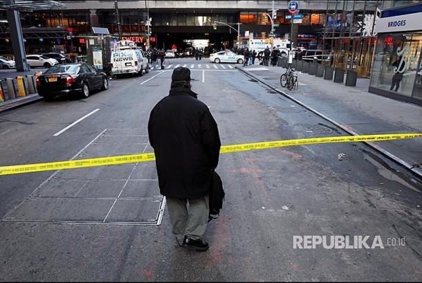 Pejalan kaki melintasi batas polisi yang dipasang di terminal bus New York City  Senin (11/12) waktu setempat.