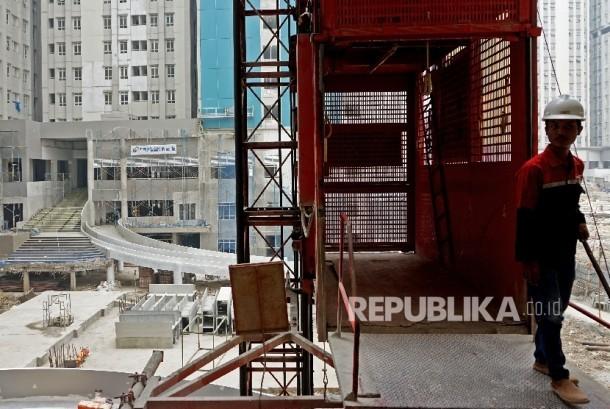 Pekerja beraktivitas disekitar proyek pembangunan rusun wisma atlet Kemayoran, Jakarta, Rabu (19/7).