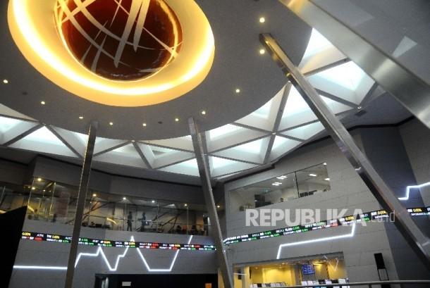 Pekerja berdiri didekat layar pergerakan Indeks harga Saham gabungan (IHSG), Gedung Bursa Efek Indonesia, Jakarta, Selasa (21/2)