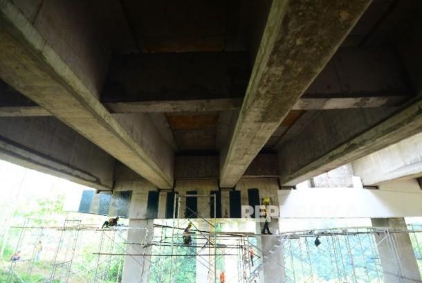 Pekerja dari Jasa Marga memperbaiki retakan pada pilar jembatan Cisomang Jalan Tol Pubaleunyi KM 100 akibat pergeseran, perbatasan Kabupaten Bandung Barat dan Kabupaten Purwakarta, Jumat (23/12).