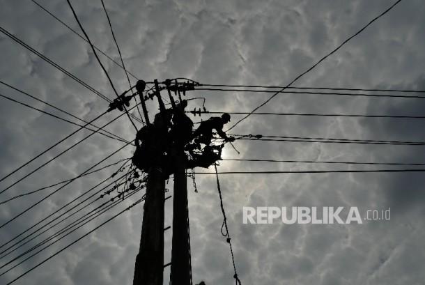 Pekerja melakukan pengerjaan perawatan dan peninggian jaringan kabel listrik (ilustrasi)