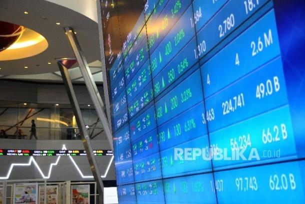 Pekerja melintas disamping layar pergerakan Indeks Harga Saham Gabungan (IHSG) di Gedung Bursa Efek Indonesia (BEI) Jakarta. ilustrasi