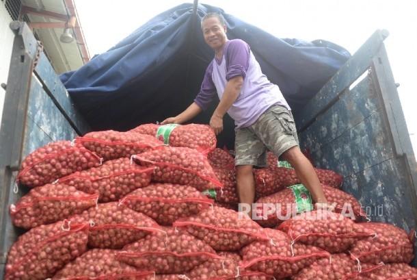 Pekerja memindahkan bawang merah yang siap dijual dalam operasi pasar di Gudang Bulog Divre Jakarta, Senin (16/5).