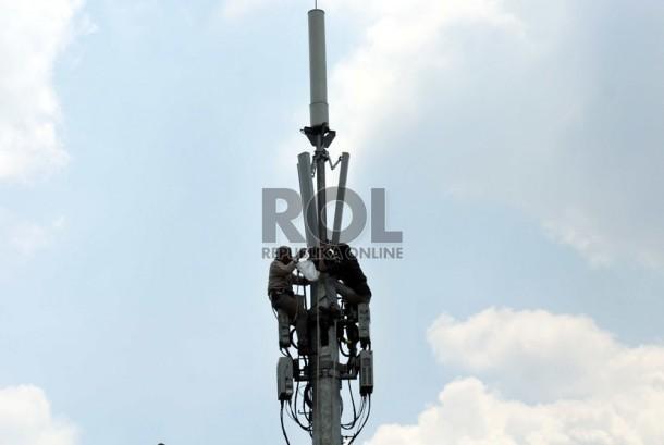 Pekerja memperbaiki menara pemancar telekomunikasi di Jakarta, Selasa (12/8).