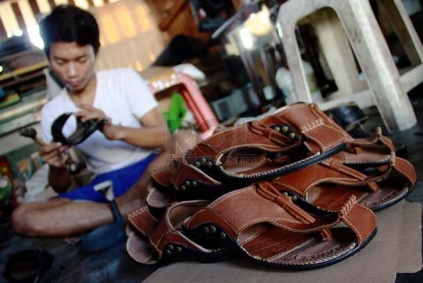 Pekerja memproduksi sepatu dan sandal kulit di bengkel rumahan Sentra Kerajinan Kulit Tanggulangin, Sidoarjo, Jawa Timur.(Ilustrasi).