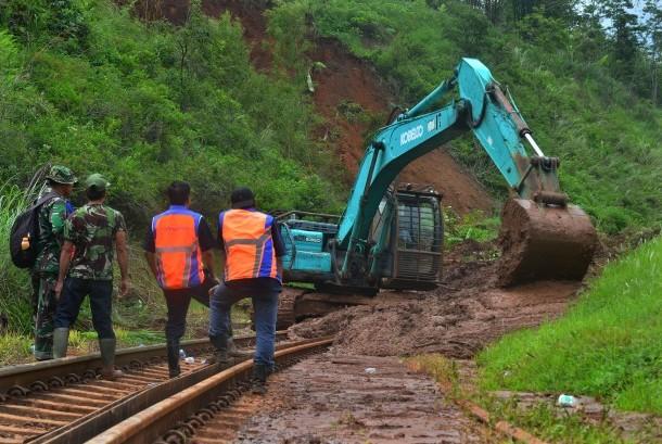 Pekerja menggunakan alat berat untuk membersihkan material tanah longsor yang menimbun jalur kereta api di KM 231+01 Malangbong, Kabupaten Garut, Jawa Barat, Kamis (23/11).