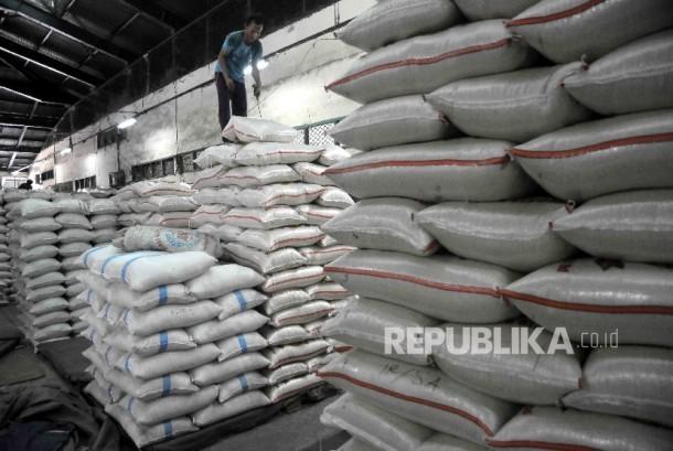 Pekerja menyusun karung beras di Pasar Induk Cipinang, Jakarta, Senin (2/1).