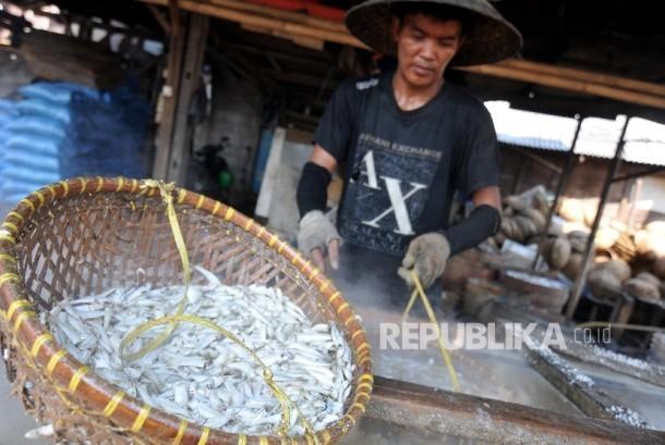 Pekerja merebus ikan dengan air garam di Cilincing, Jakarta Utara, Kamis (21/9).