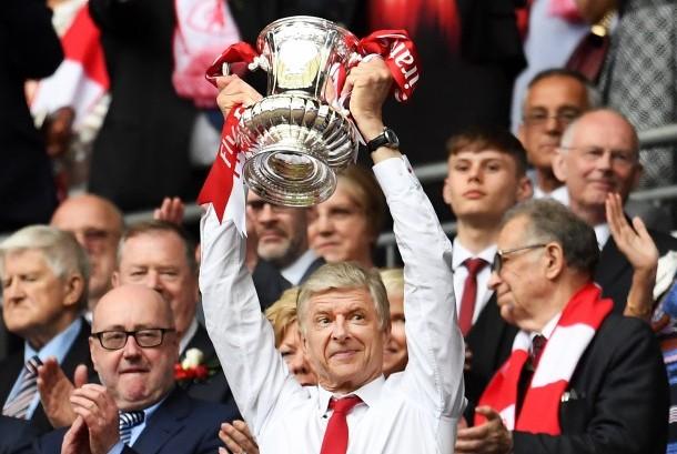Pelatih Arsenal, Arsene Wenger mengangkat trofi Piala FA setelah timnya mengalahkan Chelsea pada laga final di Stadion Wembley, Ahad (28/5) dini hari WIB.