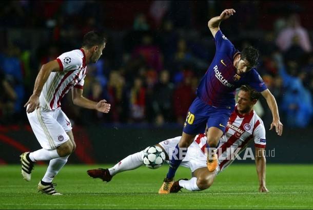 Pemain Barcelona Sergi Roberto diganjal pemain Olympiakos pada pertandingan Liga Champions Eropa Grup D di Stadion Camp Nou, Kamis (19/10) dini hari.