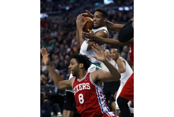 Pemain Boston Celtics, Evan Turner (tengah atas), berada di bawah kepungan pemain Philadelphia 76ers' dalam laga NBA di Boston, Amerika Serikat, Rabu (25/11).