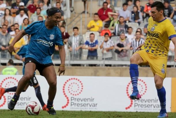Pemain sepak bola Brasil Lucio (kanan) berebut bola dengan Ronaldinho Gaucho (kiri) saat acara amal di Stadion Mineirao di Belo Horizonte, Brasil, 8 Desember 2017. Laga bertajuk 'Game of Dreams' ini juga menjadi perayaan 15 tahun Brasil meraih Piala Dunia kelima.