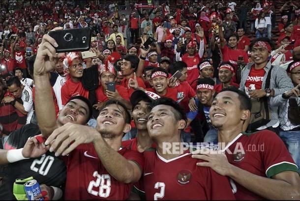 Pemain Timnas U-22 berfoto dengan suporter setelah mengalahkan Filipina pada babak penyisihan Grup B SEA Games XXIX di Stadion Shah Alam, Selangor, Malaysia, Kamis (17/8). Indonesia menang atas Filipina dengan skor 3-0.