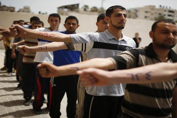 Pemuda Palestina mengulurkan tangan dengan nomor pendaftaran mereka di sebuah pusat rekrutmen kepolisian di kota Gaza.