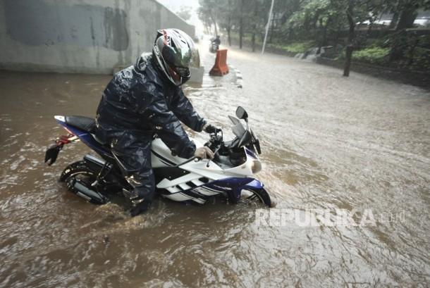 Pengendara sepeda motor melintasi banjir yang menggenangi kawasan Semanggi di Jakarta, Senin (11/12).