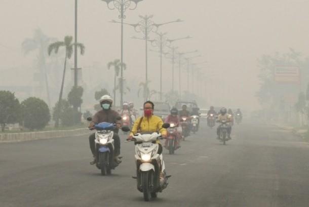 Pengendara sepeda motor melintasi jalan ketika kabut asap pekat menyelimuti Kota Pekanbaru, Riau, Minggu (4/10).