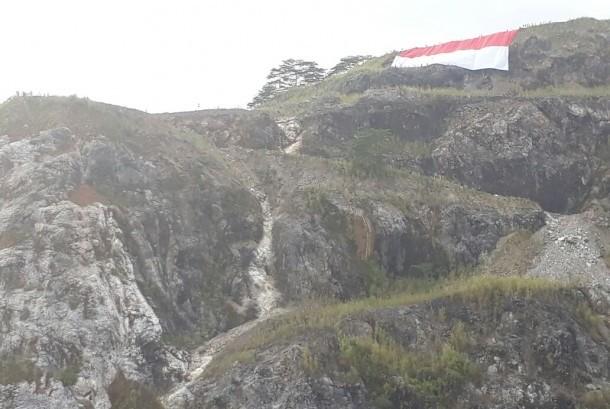 Pengibaran bendera Merah Putih raksasa dilakukan di puncak Bukit Karang Putih, area pertambangan PT Semen Padang, Kamis (17/8). Pengibaran dilakukan dengan teknik vertical rescue oleh TRC Semen Padang.