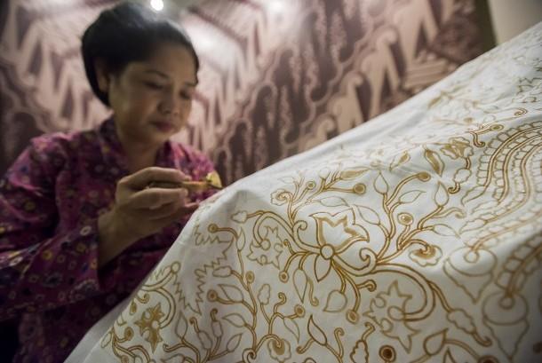 Pengrajin menorehkan lilin (malam) ke atas kain putih bermotif batik di Pameran Batik Indonesia Pusaka Dunia di Museum Nasional, Jakarta, Minggu (2/10).